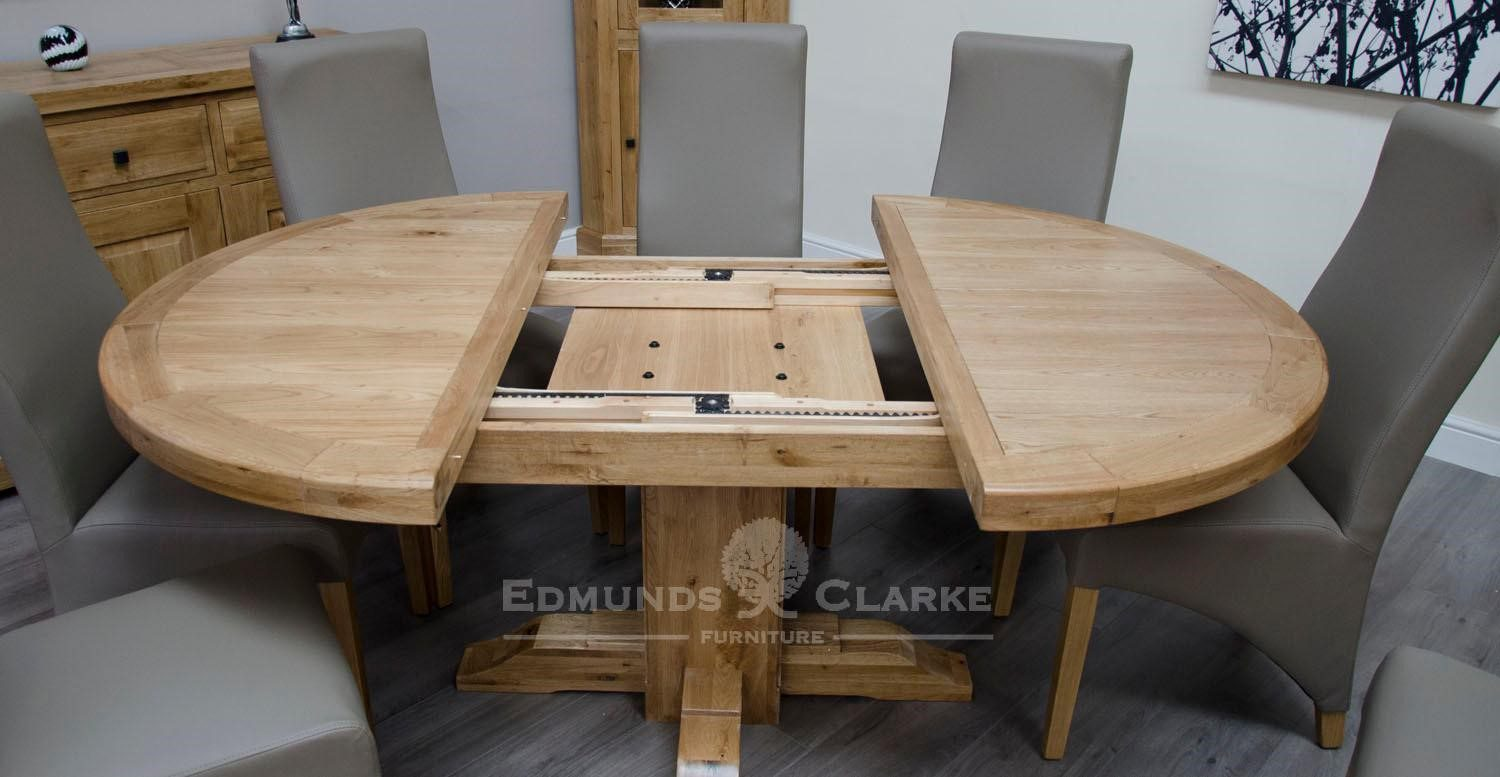Melford solid round extending table chunky rustic solid oak 167cm centre pedestal support image showing table open showing mechanisms for opening and closing, will sit 4 to 6 people comfortably DLXRNDEXT