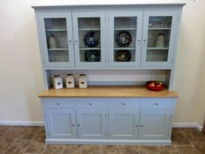 Painted 7ft Half Glazed Dresser. Handmade with solid oak top on the sideboards, painted shelves, 4 drawers with 4 large cupboards below. 4 door glazed rack above painted in southwold sky blue and satin nickel knobs. contrasting white backboards on racking EDM021
