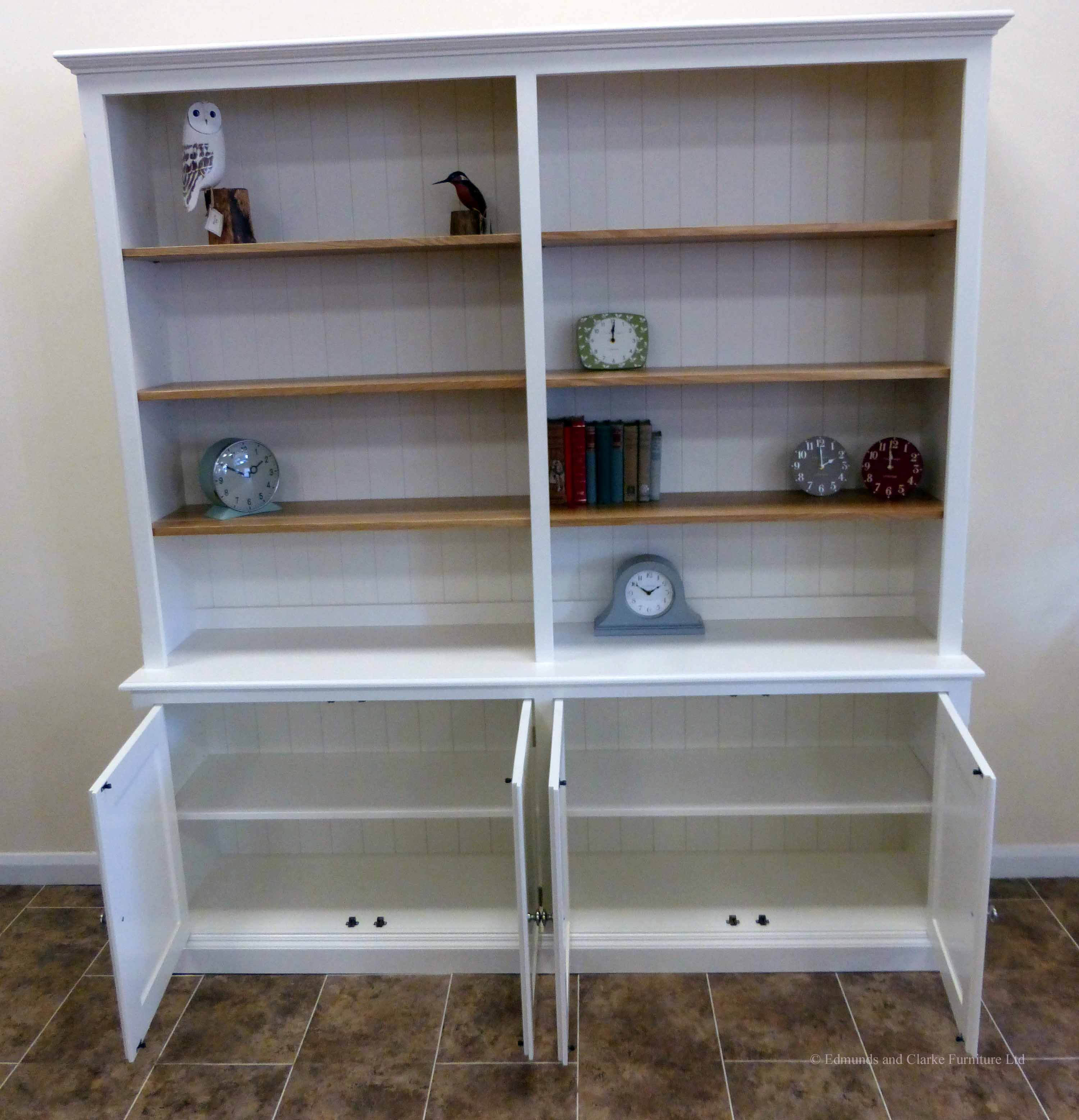 Large painted bookcase with four door cupboard below painted white with oak shelves