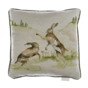 Voyage Maison Boxing Hares Cushion. two hares boxing on linen background. square with contrasting piping