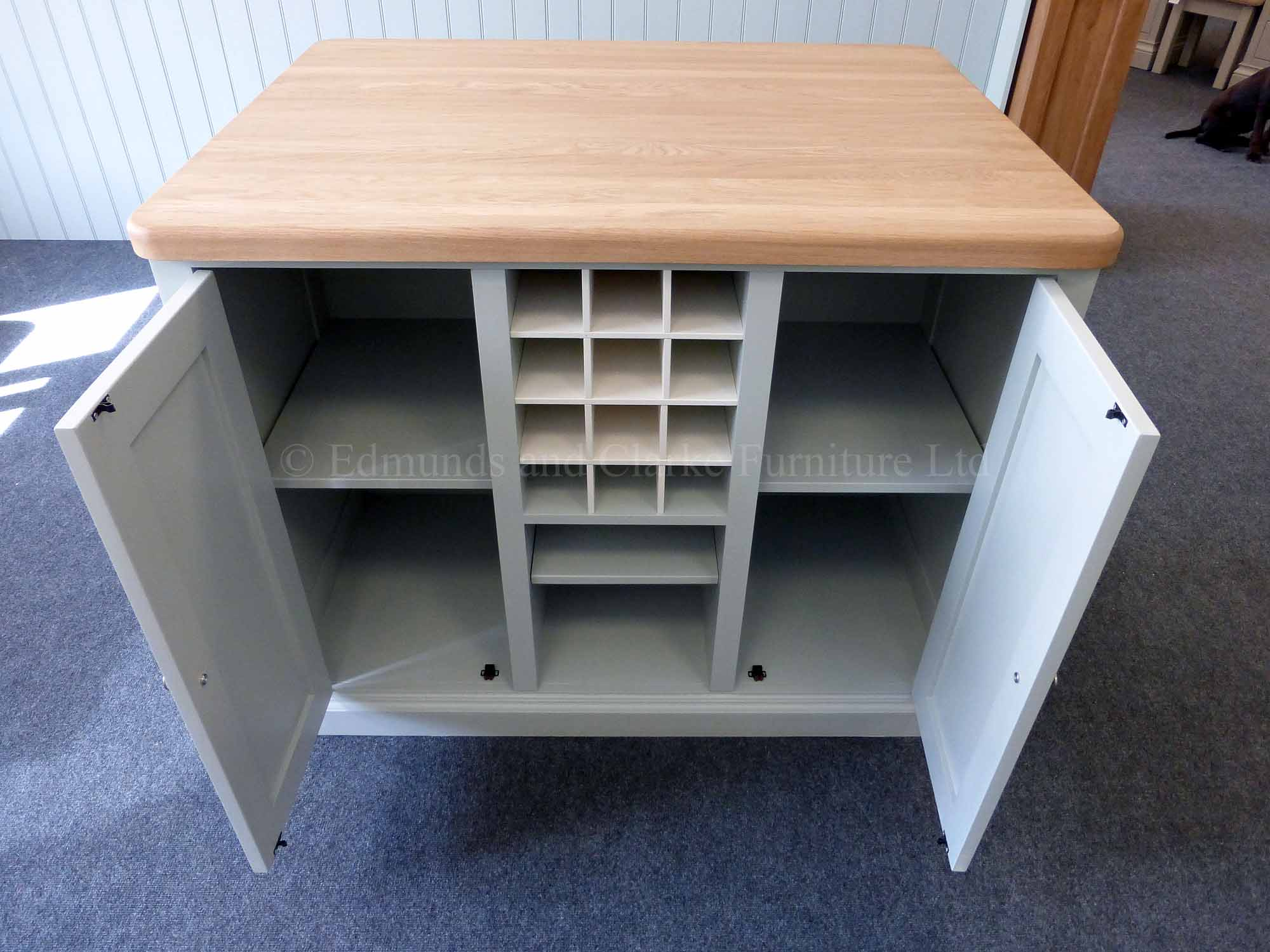 Edmunds painted 4ft x 3ft kitchen Island in Southwold Sky Blue. Solid oak top. Central shelves and wine rack with 2 paneled doors and on other side a overhang for stools. Image showing doors open EDM008