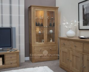 solid oak glass sided display cabinet with lights and glass shelves, two drawers below