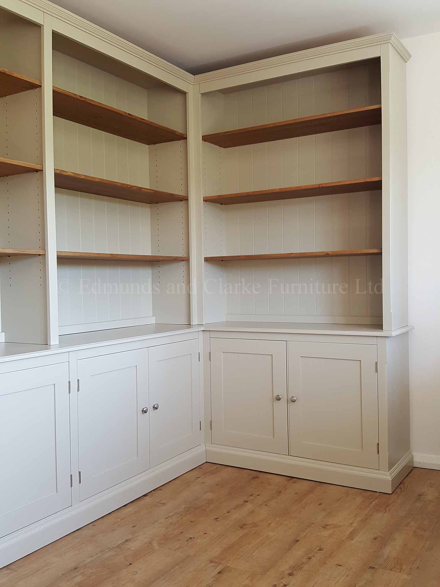 Corner library bookcase painted with wooden waxed shelves, cupboards below
