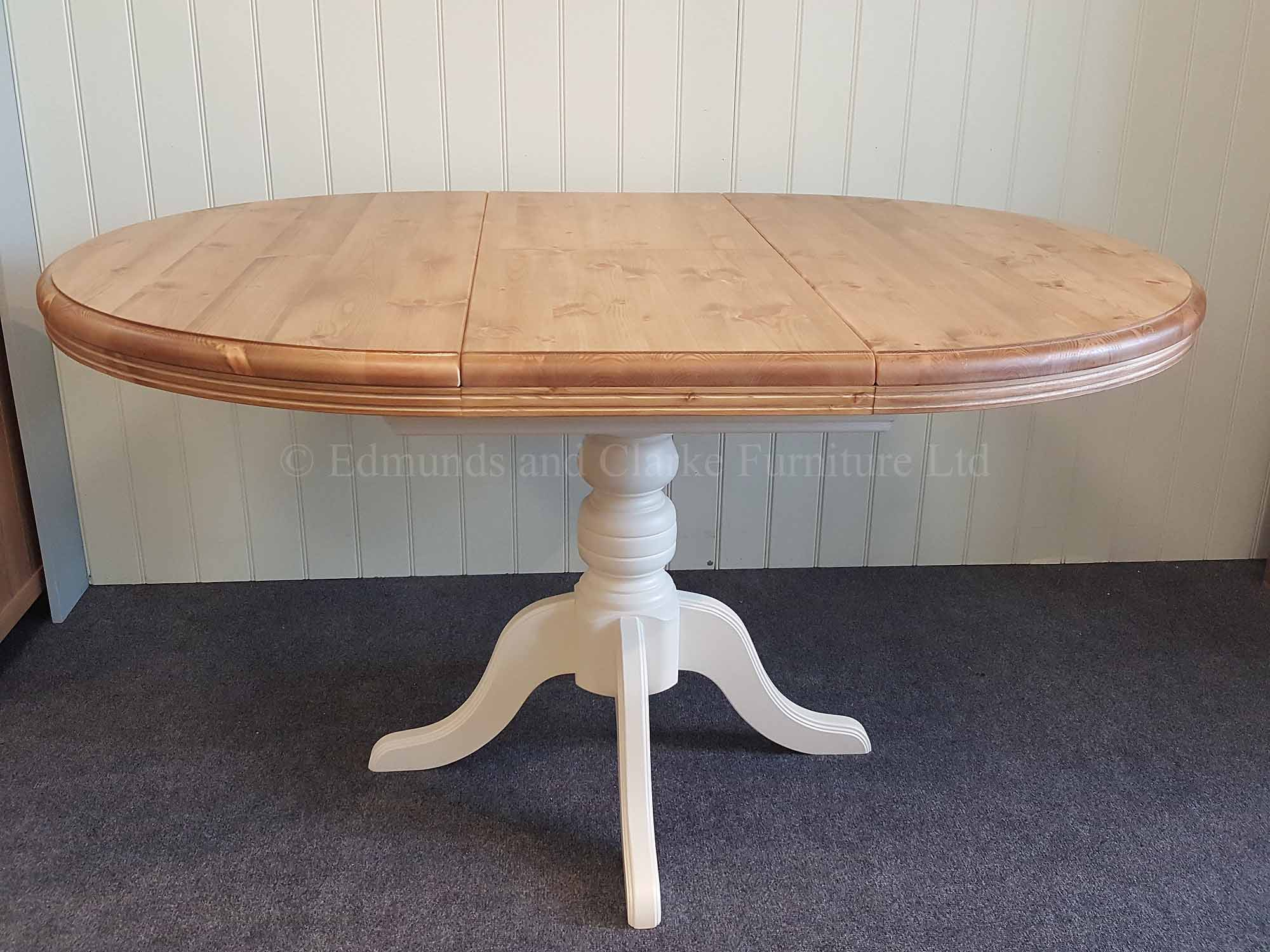 Fully extended round to oval pine and painted extending table, pine waxed top and painted pedestal