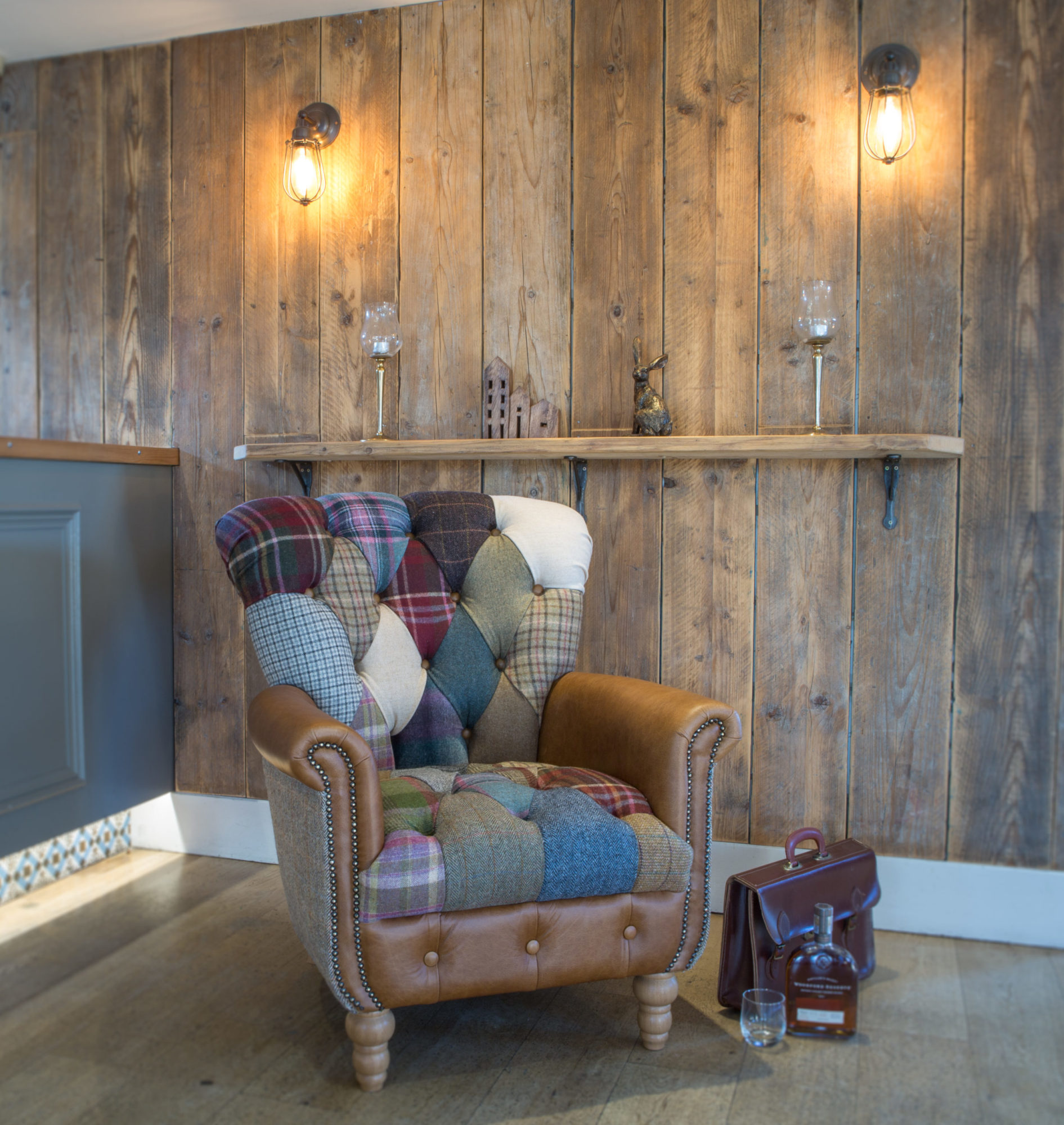 Vintage Sofa Co Gotham Harlequin Fast Track Chair in patchwork harris tweed and wool fabric with cerato brown leather arms and detailing on turned oak legs in a lifestyle setting