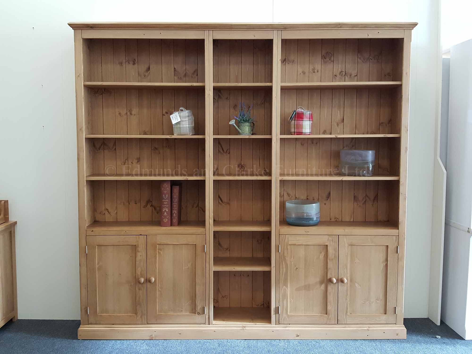 Wide three part bookcase with cupboards and open shelving 8 feet wide