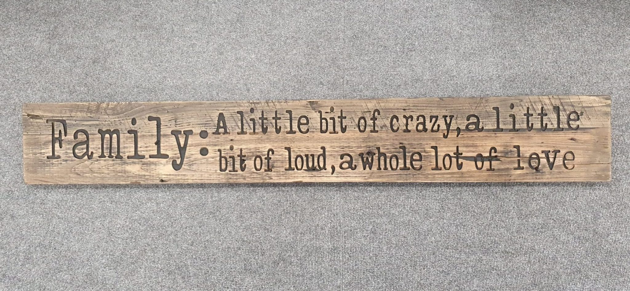 A Rustic Wooden Plaque quoting Family, A little bit of crazy, a little bit of loud, a whole lot of love, engraved