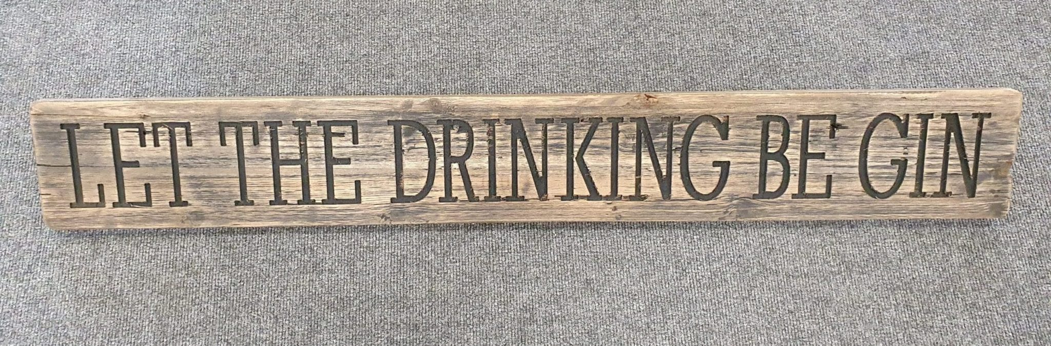 A Rustic Wooden Plaque quoting Let The Drinking Be Gin, engraved in capital letters