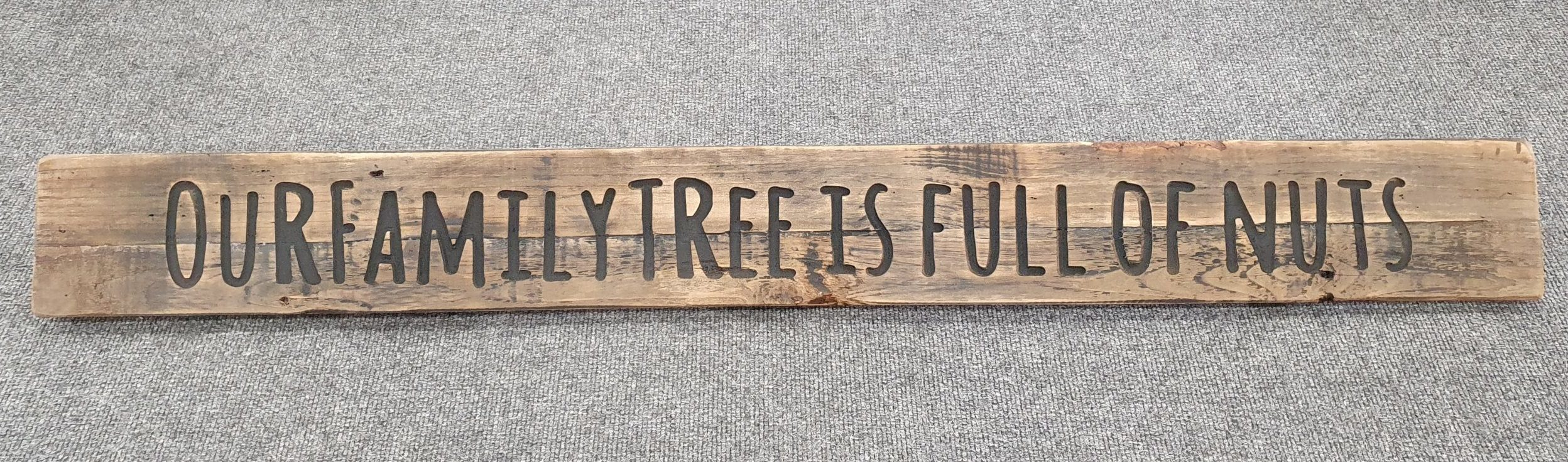 A Rustic Wooden Plaque quoting Our family tree is full of nuts, engraved in capital letters