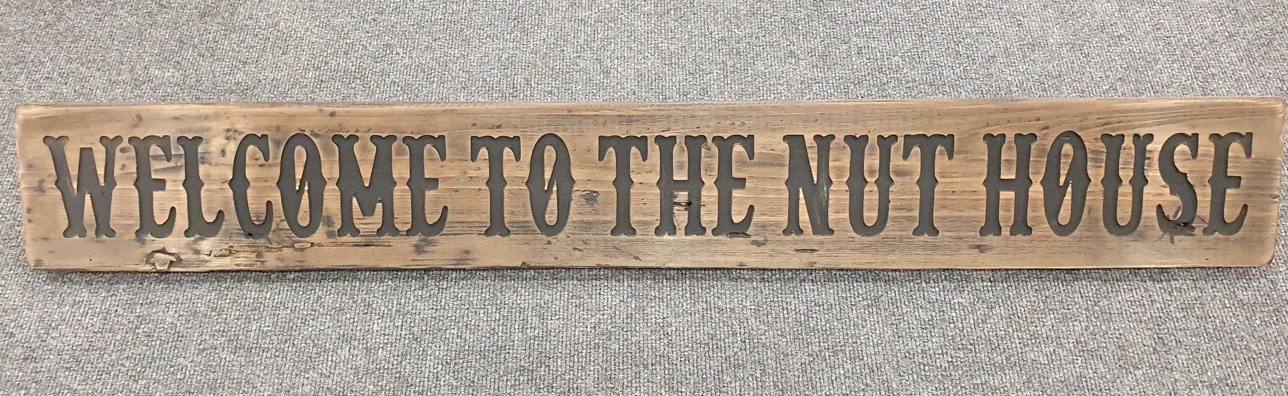 A Rustic Wooden Plaque quoting Welcome to the nut house, engraved in capital letters