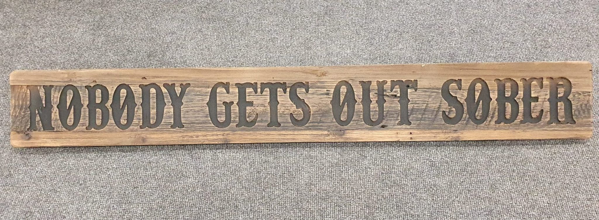 A Rustic Wooden Plaque quoting Nobody Gets out Sober, engraved in capital letters